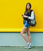 pic of rap-girl  - Happy young girl listening music  in headphones over yellowwall - JPG