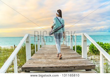 Fitness woman walking with yoga mat on beach going to outdoor meditation class at sunset. Back view