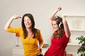 Happy teenage girls listening to music having fun together at home dancing smiling.