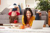 Felizes meninas adolescentes estudando em casa na sala de estar com livros e laptop.