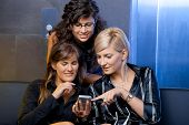 Young businesswomen sitting on couch at office lobby, looking at smart phone, smiling.