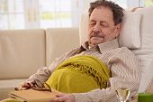Senior man lying in armchair, fell asleep while reading book.