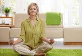 Woman sitting on floor at home doing yoga meditation.