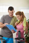 stock photo of personal trainer  - Young woman checking training plan with her personal trainer standing beside exercise bike at home - JPG