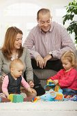image of nuclear family  - Happy family with two children playing on floor in living room at home sitting on floor in front of sofa - JPG