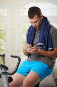 Man sitting on stationary bike at the end of training and using smart phone.