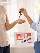 Estate agent handing over keys of new house to young owner.