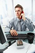 Determined businessman discussing computer work on landline phone while looking at screen typing on