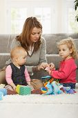 picture of nuclear family  - Mum playing on floor with two baby daughters at home - JPG