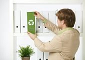 Man drawing out green folder with recycling symbol in office.?