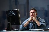 Determined businessman concentrating hard on difficult computer task working late in office looking