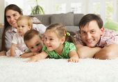 Happy family having fun posing on floor of in living room at home.?