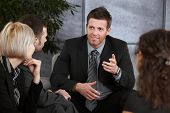 Young businessman sitting at couch in office, explaining something to others, smiling.?