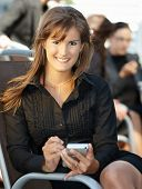 Young businesswoman sitting in chair, using smart phone.