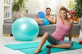 Young woman doing dumbbell exercise sitting on fittness mat at home, smiling.