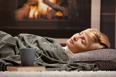 foto of floor heating  - Woman sleeping at home lying on floor in front of a fire place - JPG
