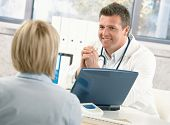 foto of doctors office  - Smiling doctor talking to patient at office desk - JPG