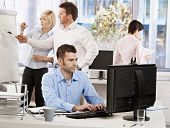 Casual businessman sitting at office desk, working on computer. Businesspeople working in background