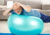 Active Senior Übungen am gymnastikball zu Hause, die Hände auf Nacken, lächelnd in die Kamera.?