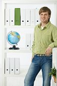 Homem jovem ambientalista no escritório olhando para câmera, sorrindo.?