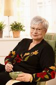 Nice pensioner lady at home having tea in bright living room, smiling at camera.