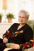 Senhora pensionista agradável em casa tendo chá na luminosa sala de estar, sorrindo para a câmera.