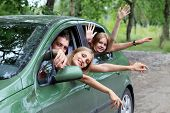 stock photo of road trip  - Cheerful young people having summer trip on a car - JPG