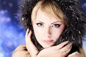 Portrait of a beautiful young woman over sky of stars and snow.