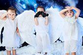 Beautiful little angels looking through a binocular,  snowy background.