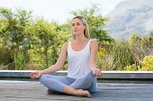 Woman practicing yoga and meditating outdoors. Mature woman relaxing with lotus yoga position in the poster