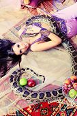 Shot of an oriental woman posing with a python.