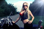 Shot of an attractive woman biker posing near her motorcycle.