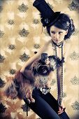 Portrait of a fashionable lady with a dog over vintage background.