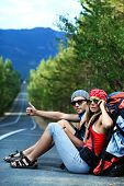 Two young people tourists hitchhiking along a road. poster