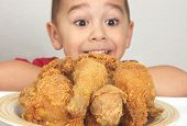 stock photo of fried chicken  - A plate of fresh fried chicken with a boy looking on  - JPG