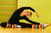 stock photo of leg warmer  - Ballet dancer doing stretching exercise on a floor - JPG
