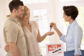 picture of real-estate agent  - Estate agent handing over keys of new house to smiling couple - JPG