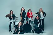 Teen Music Band Performing In A Recording Studio. The Group Of Girls Standing Together And Posing At poster