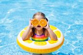 Child In Swimming Pool. Kid Eating Orange. poster