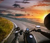 POV of motorbiker holding steering bar, riding in Alps in beautiful sunset dramatic sky. Travel and  poster