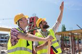 Confident and determined young worker pointing up while imagining with his colleague the height of a poster