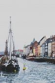 Copenhagens Famous Nyhavn Harbour With The Typical Colorful Houses And Restaurants Along The Iced C poster