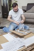 The Man Kneels On The Carpet Above The Cardboard Box With Elements Of Furniture For Self-assembly An poster