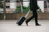 Midsection Of Motion Handsome Young Business Man In Modern Suit Walking With Big Black Luggage Trave poster