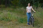 Young Woman Riding On Bicycle In The Forest. Leisure On Cycle, Active Lifestyle, Cycling In Park poster