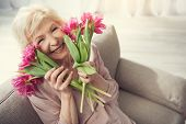Elderly Female Person Sitting At Home With Tulips And Looking At Camera With Bliss. Copy Space In Ri poster
