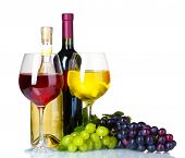 Ripe grapes, wine glasses and bottles of wine isolated on white