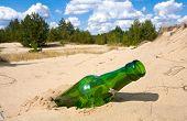 Green Glass Bottle In Sands