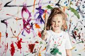Cute child with smuges of colorful paint showing a paint brush. Little artist. poster