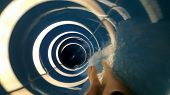 Person Going Down A Blue Water Slide With White Rings And Into A Tube At A Water Park Aqua Park. Sum poster